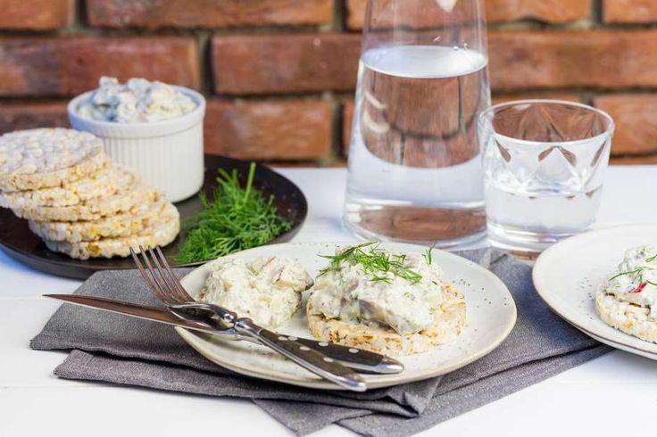 Recept voor smørrebrød voor 4 personen. Met zout, peper, haring, appel, rijstwafel, zure room, mayonaise, Dijon mosterd, dille, kappertjes, sjalot en boter