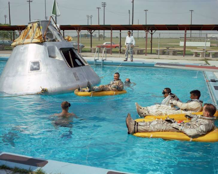 In this June 1966 photo, the Apollo 1 crew practices water evacuation procedures with a full scale model of the spacecraft at Ellington AFB, near the then-Manned Spacecraft Center, Houston. In the rafts at right are astronauts Ed White and Roger Chaffee, foreground. In a raft near the spacecraft is astronaut Virgil Grissom.