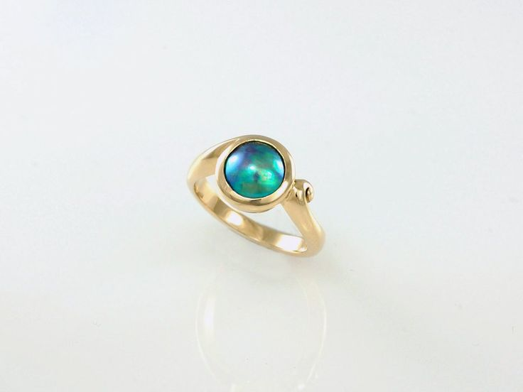 """New Zealand Blue Pearl Ring. Stylish and feminine this beautiful iridescent 8mm A grade Blue pearl ring is timeless. Set in 9ct yellow gold, the soft curls of the ring inspired by the """"Koru"""" (spiral) represent the unraveling of the fern leaf. A symbol of """"new beginnings"""".   Jewellery made @jewelbeetle in Nelson, New Zealand."""