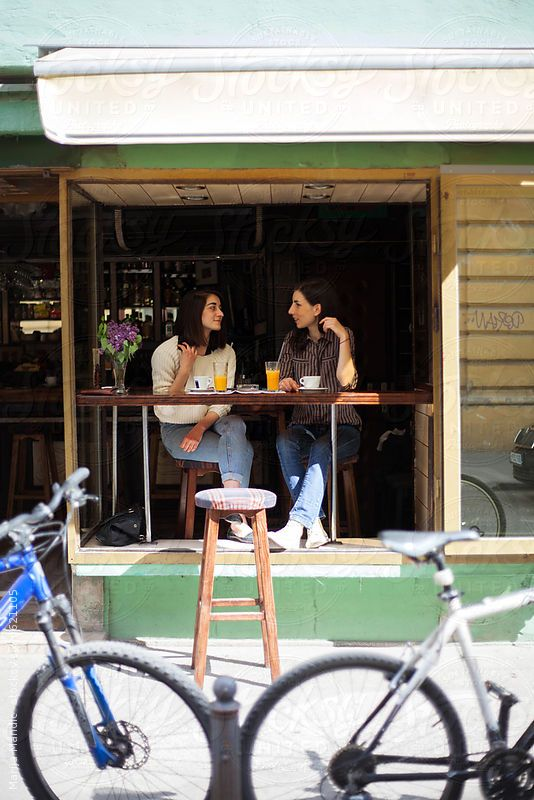 Two woman drinking coffee at the cafe during the sunny day