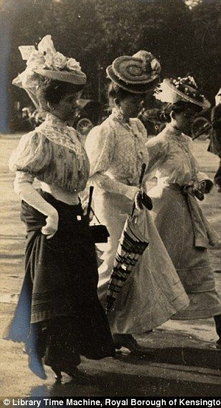 A group of women holding parasols and wearing eyecatching hats walk along the Champs-Élysées, Paris, June 3rd 1906.