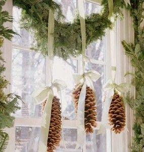 A green holiday window treatment; pinecones,ribbons and natural garland.