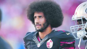 Colin Kaepernick of the San Francisco 49ers stands...