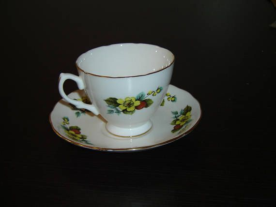 "The design is a yellow flower and red berries with blue and green leaves, gold banding on the edges  The cup is 2 11/16"" (6.8 cm) high x 3 7/16"" (8.7 cm) at the brim and the saucer is 5 1/2"" (14 cm) in diameter  The cup is numbered E 66 7 and the saucer is numbered E 66 8  This set is in near mint condition and doesn't seem to have seen use as anything other than a collectible  Made of bone china from England by Royal Vale    These items have no nicks, chips, cracks, or signs of repair…"