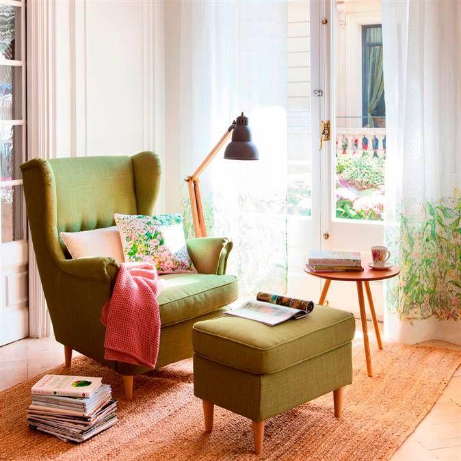 Butaca orejera con reposapiés a juego, mesita de madera, lámpara de pie articulada, alfombra yute y libros