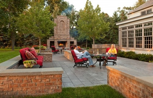 Outdoor rooms paved with poured and sandblasted concrete and concrete landscape tiles. The ground-level patio connects to the home by two raised patio decks. The outdoor spaces are defined by low brick seat walls capped with blue stone.