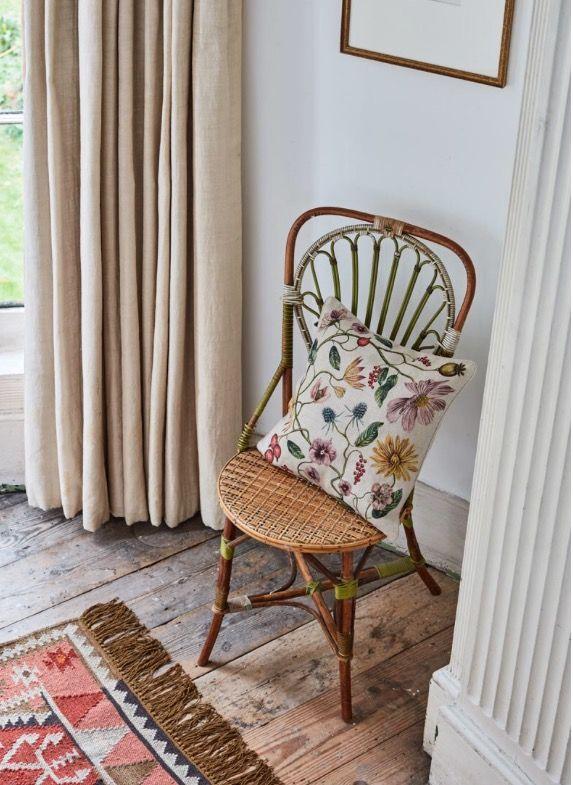 Rustic wood floors, white walls, rattan chair, cream linen curtains