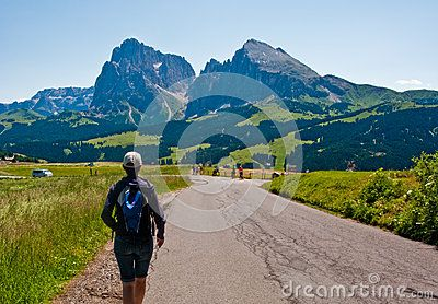 Woman hiking in Italian Alps, heading towards The Sciliar mountain range. Alpe di Suisi.