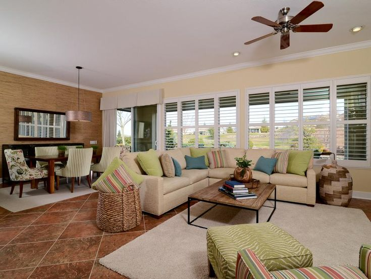 Tropical elements infuse this transitional family room with texture and color. A large sectional sofa provides plenty of seating for family and friends, while a dining table offers a spot for informal meals and impromptu games.