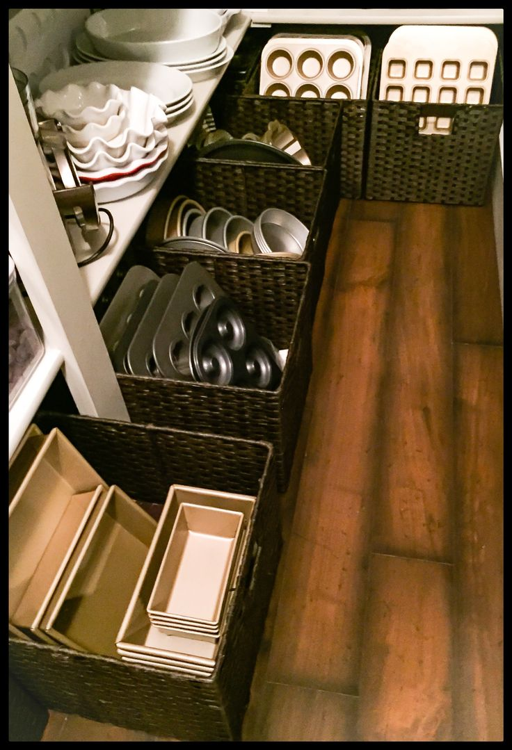 Pantry Storage - woven, easy-to-clean bins are used to organize baking sheets and trays in the pantry - via Everything Emmy
