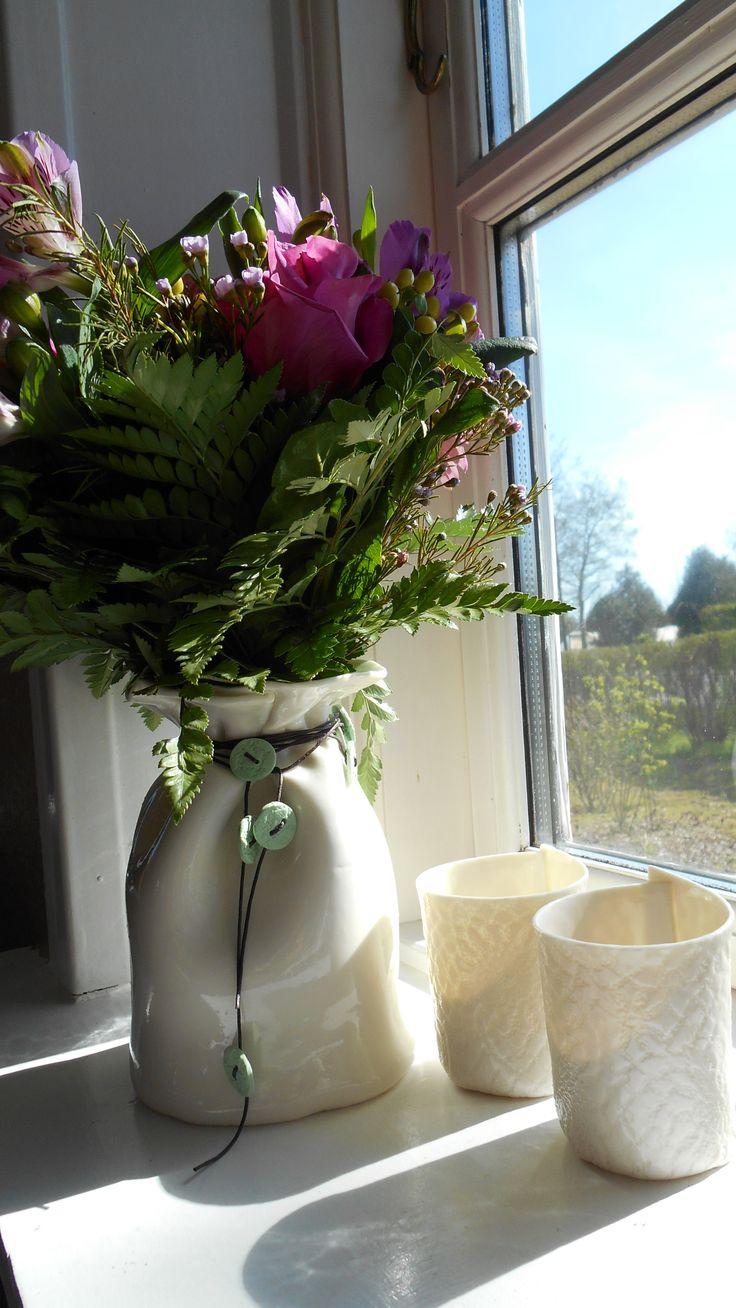 Light-House lysestager sammen med en Baggy-vase. Baggy-vasen er pyntet med indfarvede porcelænsknapper i lædersnor.