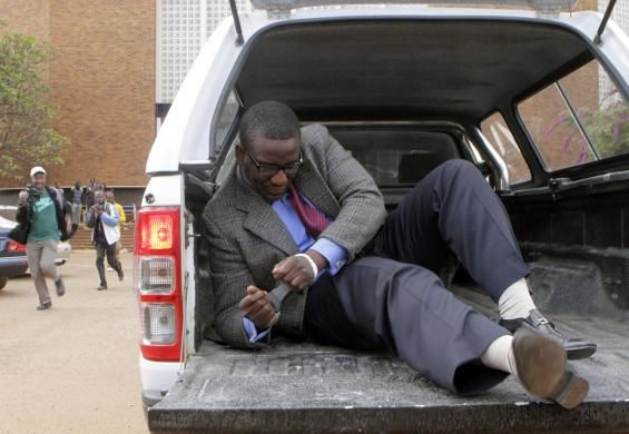 Editor of the state-run Sunday Mail newspaper Edmund Kudzayi gets out of a police vehicle as he arrives at the Harare Magistrates court, where he was charged with attempted terrorism, insurgency and banditry June 21, 2014. REUTERS/Philimon Bulawayo