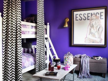 Contemporary white bunk beds are tucked behind black and white chevron curtains.  The bold patterned curtains pop against the vibrant purple walls making for a chic rock 'n roll bunkroom.