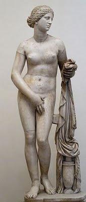 """También conocida como """"Afrodita de Cnido"""" es una de las piezas más famosas de Praxíteles, un escultor griego del período helenístico. Una pieza realizada en Atenas que se nos presenta como diosa del amor y que simboliza la belleza y la fertilidad femenina. Se trata de la primera representación que conocemos de un desnudo femenino en la historia del arte griego."""