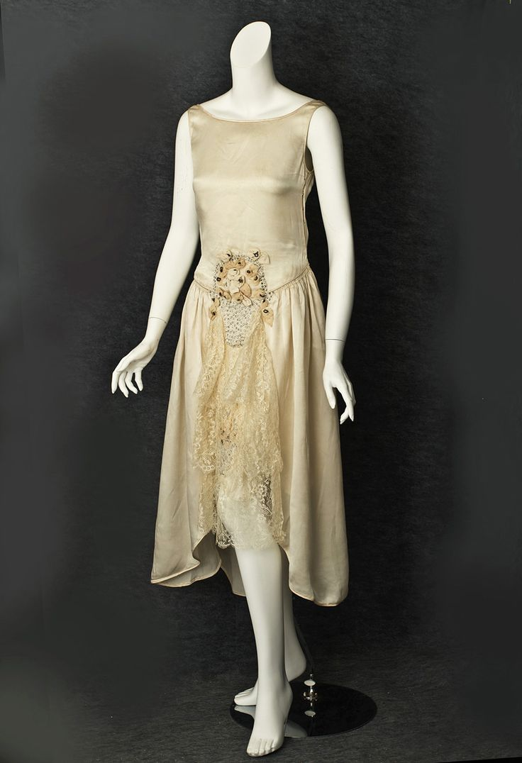 French Flapper Wedding Dress Made Of Champagne Colored Satin With Three Tiers Of Matching Lace On The Skirt Front, Uneven Hemline, Rhinestone Basket Of Ribbon Art Roses With Metallic Cord Centers, Smaller Basket Of Flowers Peeking Through The Lace Just Above The Knee - Made In France For A Roanoke, Viriginia Store   c.1928  -  Vintage Textile