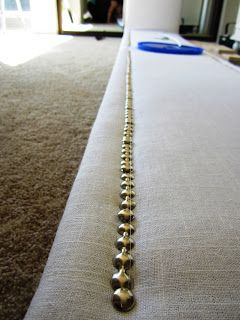 Use fishing line wrapped around the two ends of nailhead trim to keep the line straight.  http://diydithering.blogspot.com