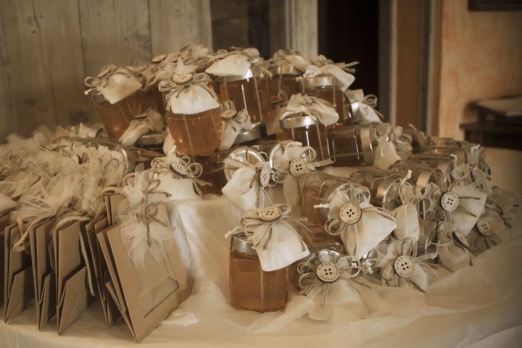 vasetti di miele confezionati con sacchettini in organza e lino, fiocchi grezzi e bottone il legno decorato