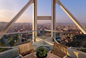 Two chairs on a deck with a panoramic view of a city
