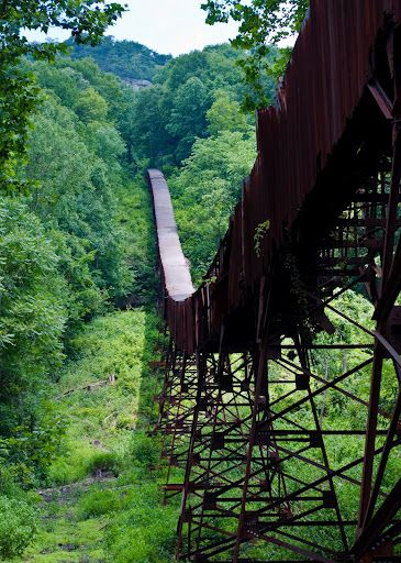 Nuttallburg, West Virginia - in the early 1920s, Henry Ford purchased the lease to the Nuttall Coal Mine and modernization of the mine's buildings began. Two of these structures were the tipple and belt line. The belt line was used to haul coal from the mine opening halfway up the steep wall of the gorge, all the way down to the tipple. The tipple was used to load coal into waiting train cars where it would then be shipped off to other destinations across the country.