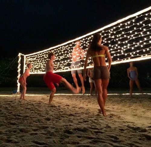 String lights on a volleyball net at night, great idea for birthday or spring/summer party for teens, tweens, youth or church groups. Perfect for an end of the school year party celebration!