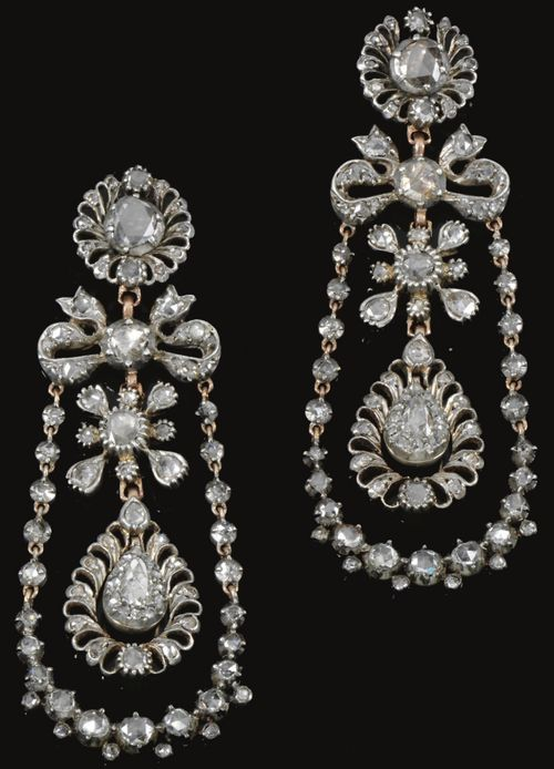 A pair of antiquediamond pendant earrings, circa 1800. Each of stylised foliate and ribbon design, suspending a chain of rose diamonds in cut down collets and closed back settings, embellished with a swing set to the centre with a pear-shaped rose stone within surrounds of rose diamonds.