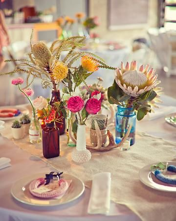 Arrangements of antlers, cacti, and glass vases holding garden roses, pincushion, and king protea at a wedding in Marfa, TX