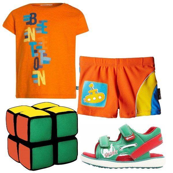Maglietta manche corte arancione con scritta colorata, costumino arancio con disegno di un sommergibile che riprende i colori della maglietta, sandali primi passi verdi e rossi e cubi colorati morbidi per giocare in relax sotto l'ombrellone.