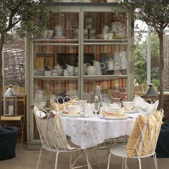Vintage furniture, shabby chic furnishings and French-style accessories create a country style in this conservatory. The eclectic mix of styles gives the room a laid-back feel.