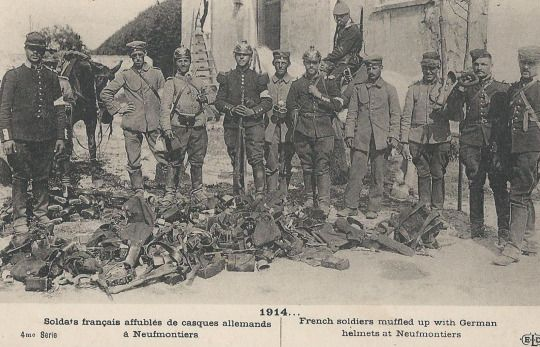WWI, 1914; French soldiers muffled up with German helmets at Neufmontiers.