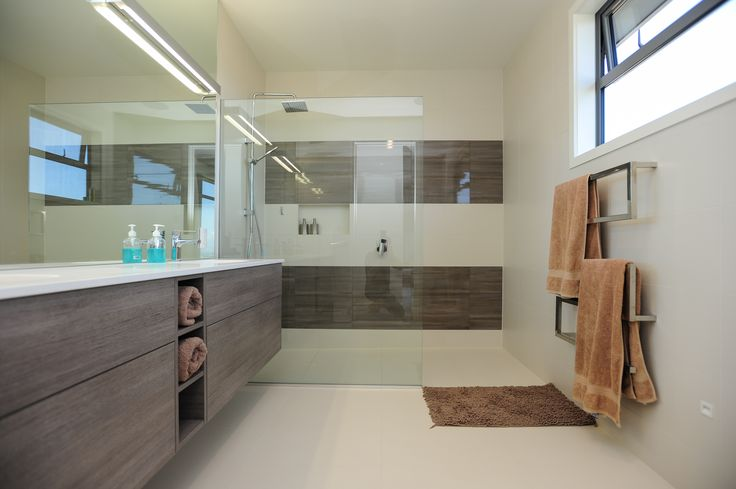 A custom built vanity together with wood look panels in the shower of this wet room.