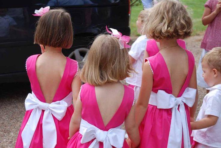 enfants d'honneur rose: es demoiselles d'honneur sont vêtues de robes rose vif à large noeud blanc. Les emmanchures sont bordées de croquet et le dos est très échancré.    Accessoires:  barrettes à double noeud d'organza rose et blanc, espadrilles blanches.