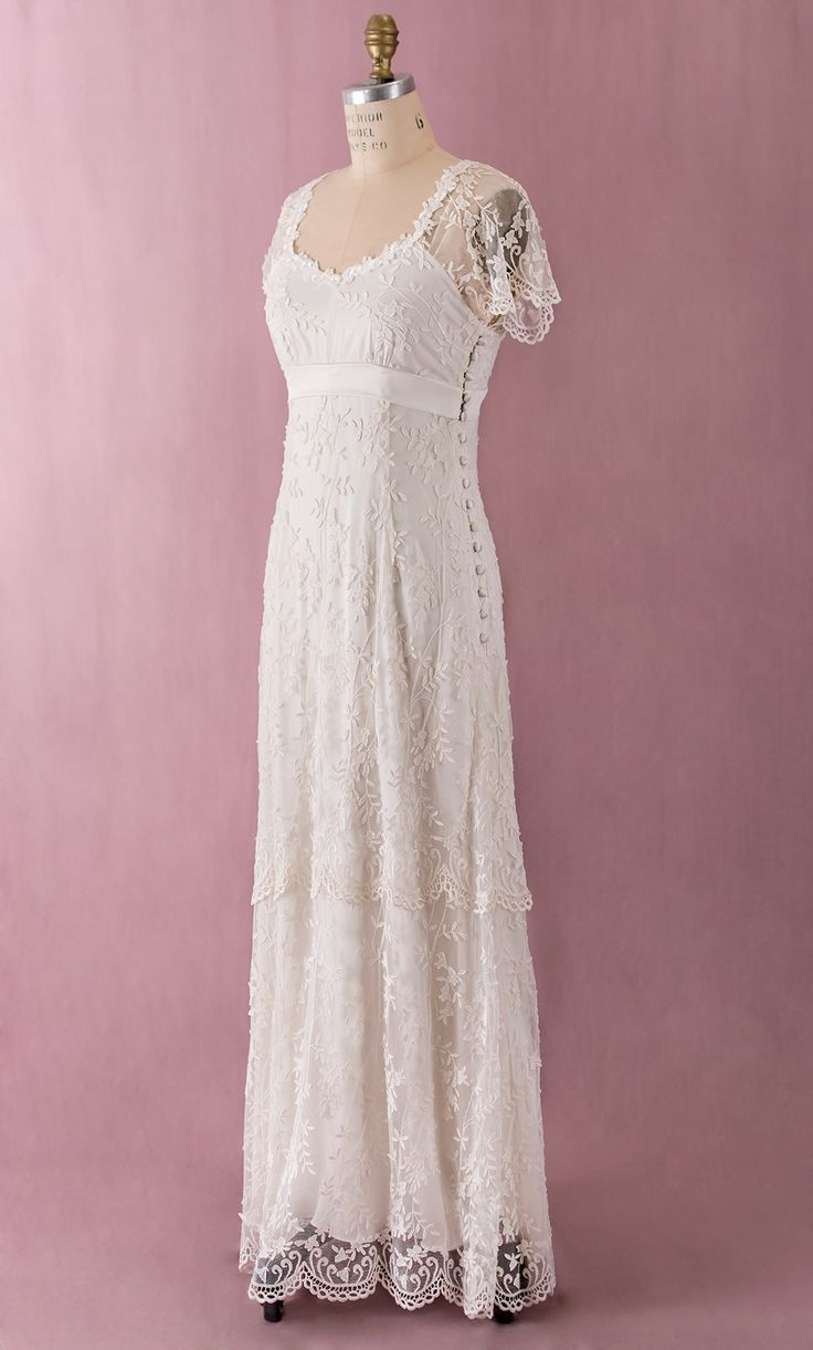 Estelle by Martin McCrea   Wedding dress made of scalloped embroidered tulle with a leaf-and-vine motif, lined with silk charmeuse. Features a side button & loop closure and cap sleeves. Silk charmeuse band at the empire waistline gives this gown a very flattering fit.
