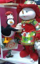 Muñeca de nieve y pingüino regalando cupcake