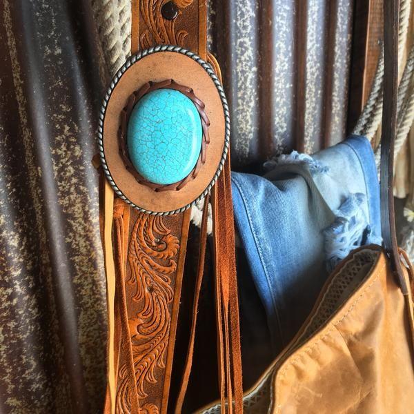 The Oswego - Retro leather fringe handbag. Soft rich saddle tan leather. Long fringe sides. Adjustable Leather and turquoise stone buckle on strap. Distressed tooled leather belt strap. Earth tone southwest fabric lined. Interior pocket. Magnetic snap closure. Everything retro we love!