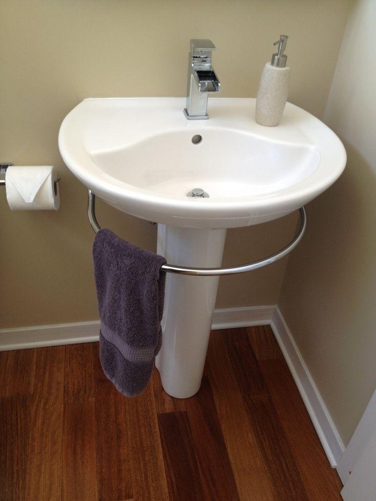 White Pedestal Sink With Towel Bar And Purple Towel Plus Tissue Holder