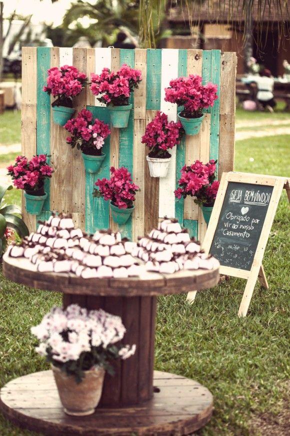 """Utilizar o """"carretel"""" com o vaso em baixo para colocar o bolo e o painel de palet (com hortencias azuis) para embelezar a mesa de doces."""