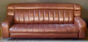 Africa then & now - Provenance Auction House: A Danish Strouby Leather Settee. Fold over back, shaped arms, on metal feet.