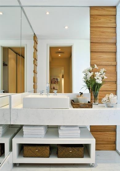 A combinação de branco e madeira é uma ótima opção para banheiros. A organização com cestas e o arranjo de flor deram o toque final para o bom gosto desta ambientação.