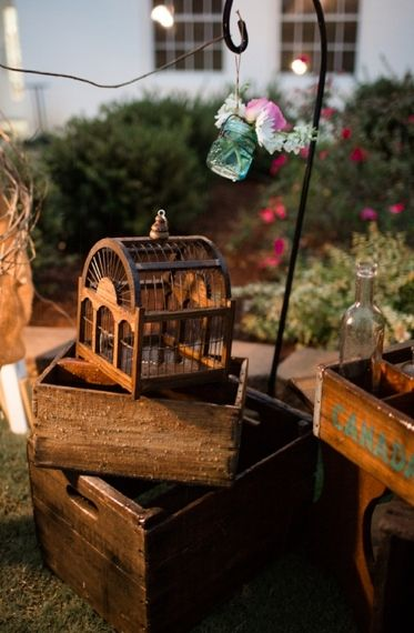 An antique bird cage and varnished crates add a romantic and rustic touch to wedding decor.