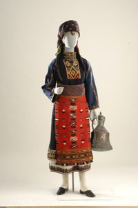 With some variations, this costume was the festival dress worn by married as well as single women. It was customary in the 11 villages of the Kavakli district in Eastern Rumelia, which is now part of Bulgaria. After the population exchange of 1922-23, its inhabitants settled in Thessaly, Macedonia and Thrace. The main component of this costume is the tsoukna, a sleeveless one-piece dress with an embroidered hem whose type of embroidery, patterns and colors denoted the social situation of the…
