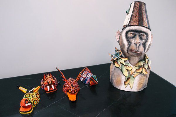 """Guatemalan miniature masks share a surface with """"Monkey in Fez,"""" a sculpture from Ardmore Ceramic Art in South Africa. """"I love masks and all kinds of animal imagery,"""" Mr. Rockefeller said."""