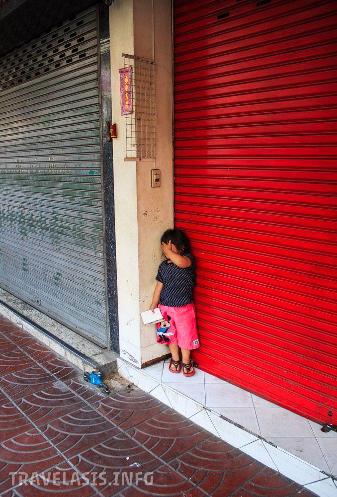Тайская девочка играет в прятки, китайский квартал Бангкок
