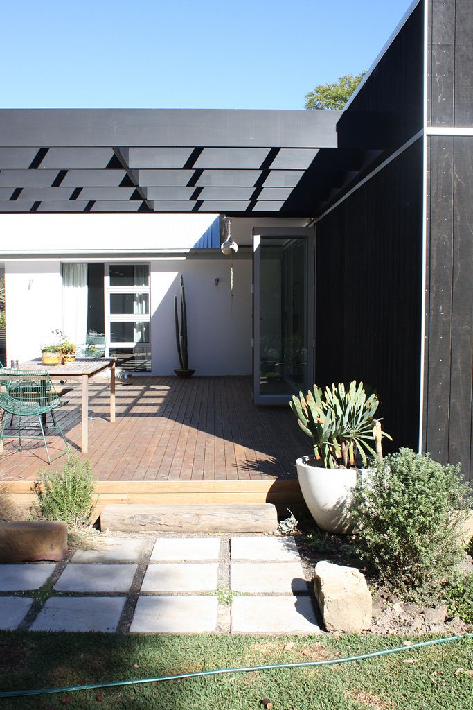 The lattice squares of the black pergola, which serves to extend the line of the house and create of seamless flow between inside and out, is echoed in the windows and paving stones.
