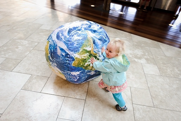 A young girl pushes an inflatable ball depicting Earth