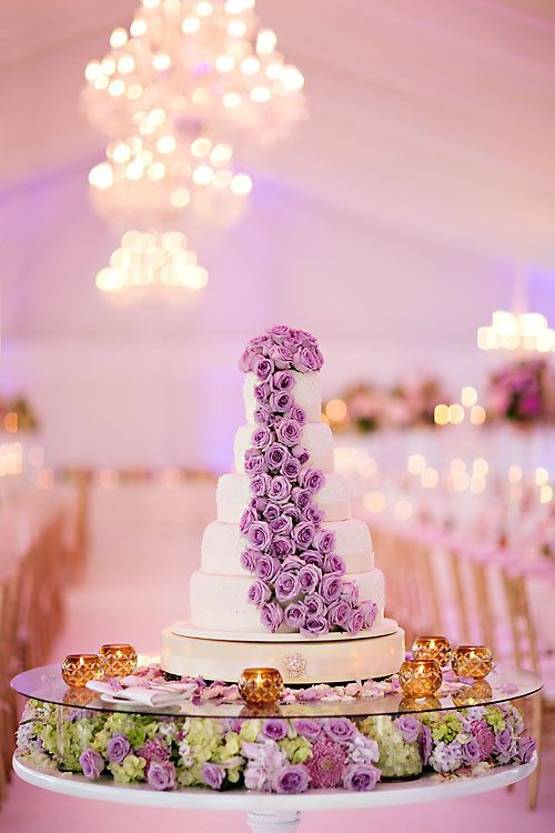 Cake installation, and what an installation it was boasting flavours of vanilla, passion fruit, and Ferrero Rocher! The wedding cake consisted of 5 tiers complete with brooch and ribbon detail, tiers stacked one above the other with a band of flowers cascading from top to bottom. And positioned in the centre of a glass top with a bed of hydrangeas, roses and chrysanthemums completed the display!  Wedding co-ordinator: www.weddingsbymarius.co.za