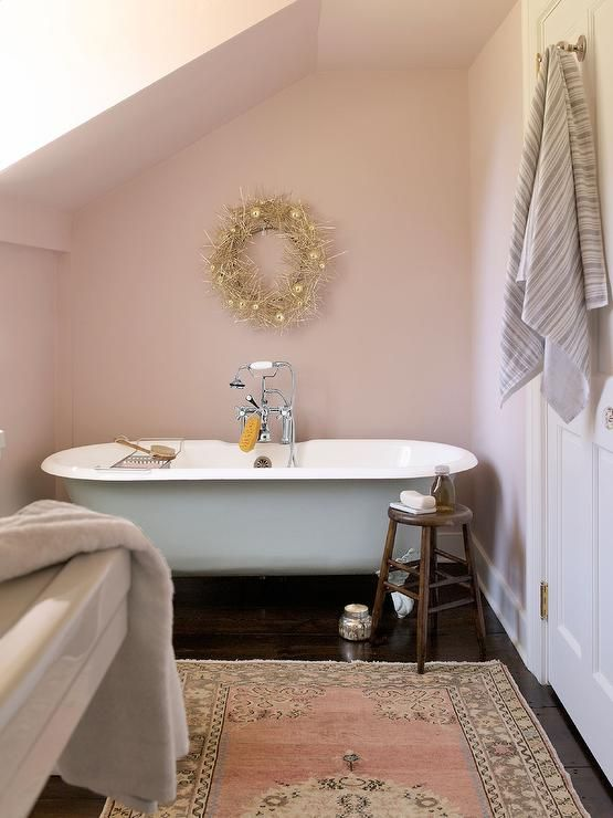 This pink country bathroom, featuring pink walls in Farrow & Ball Calamine and ebony wood floors dressed in a pink wool rug, boasts a freestanding clawfoot tub accented with a polished nickel tub filler and sat beneath a gold wreath mounted on a wall under a sloped ceiling.