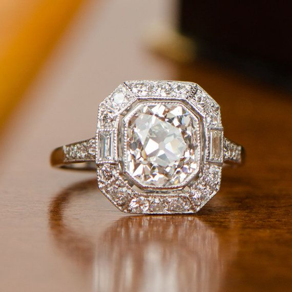 Centering this exquisite engagement ring is a breathtaking 2.80 carat antique cushion cut, J color, and VS2 clarity diamond. Surrounding the center diamond is a halo of diamonds. Two baguette cut diamonds flank the center stone. This ring is entirely hand-crafted in platinum.  Center Cut: Antique Cushion Cut Center Weight: 2.80 Clarity/Color: J/VS2 Material: Platinum