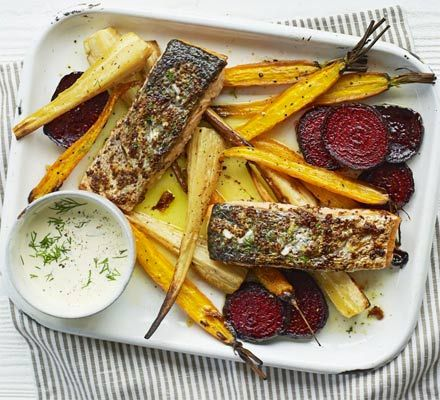A rustic fish tray bake with a root vegetable base of parsnips, beetroot and carrot - served with a creamy dill sauce
