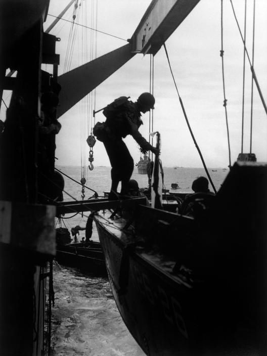 Robert Capa June 6th, 1944  Off the coast of Normandy American troops transfer from troop ships to landing craft before assaulting Omaha Beach.