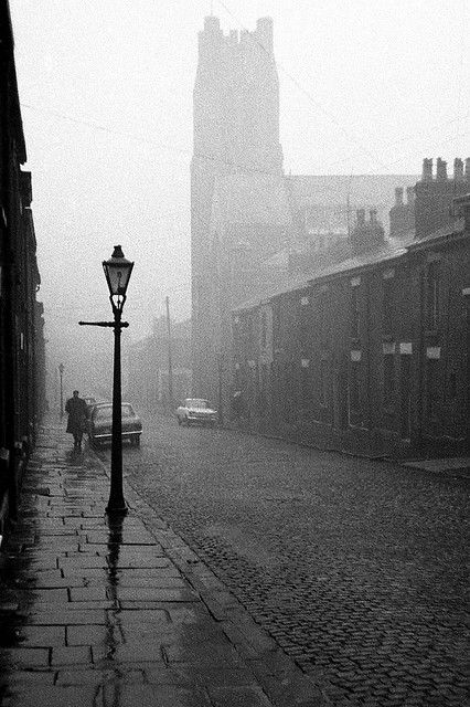 (TRAY- Photographed just in time.Most demolished early 1970s- Asda Superstore -St.Thomas's church still there.) Raglan Street-?-street off Eccleston Street ) Red-brick Victorian church, rainy flagstone pavements, gas lighting, long terraces of slate-roofed houses, stone setts  and, dimly visible through the murk, a corner shop. A perfect Lancashire industrial townscape, complete and intact when this picture was taken on 12th December 1969.Fray Bentos Stephen Dowle